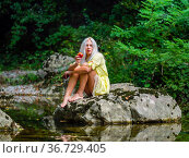 Attractive blonde woman on a Green forest river with an apple in hand. Стоковое фото, фотограф Emil Pozar / age Fotostock / Фотобанк Лори
