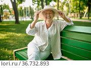 Granny in hat sitting on the bench in summer park. Стоковое фото, фотограф Tryapitsyn Sergiy / Фотобанк Лори