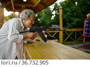 Grandma with gun poses in shooting gallery. Стоковое фото, фотограф Tryapitsyn Sergiy / Фотобанк Лори