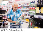 old age man examines bottle of vermouth in alcoholic section of supermarket. Стоковое фото, фотограф Татьяна Яцевич / Фотобанк Лори