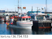 Small fishing boats stand moored in port (2017 год). Редакционное фото, фотограф EugeneSergeev / Фотобанк Лори
