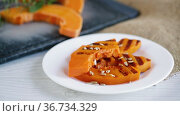 Sweet baked grilled pumpkin with seeds in a plate. Стоковое видео, видеограф Peredniankina / Фотобанк Лори