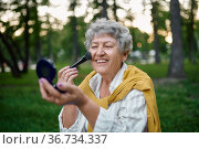 Pretty granny does makeup in park, back to yout. Стоковое фото, фотограф Tryapitsyn Sergiy / Фотобанк Лори