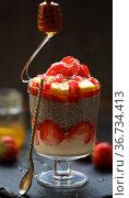 Dessert with chia, yogurt, honey, strawberries, pomegranate on a black background. Стоковое фото, фотограф Марина Володько / Фотобанк Лори