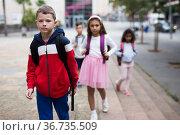 Tween boy with backpack walking to school campus after lessons. Стоковое фото, фотограф Яков Филимонов / Фотобанк Лори