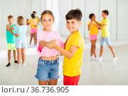 Tween boy and girl practicing slow pair dancing during group class. Стоковое фото, фотограф Яков Филимонов / Фотобанк Лори