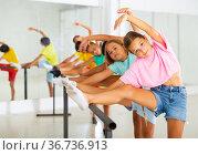 Diligent tween girl practicing classic dance moves near ballet barre. Стоковое фото, фотограф Яков Филимонов / Фотобанк Лори