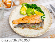 Fried trout fillet served with avocado is healthy dish in kitchen. Стоковое фото, фотограф Яков Филимонов / Фотобанк Лори