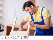 Young male carpenter repairing chair in the office. Стоковое фото, фотограф Elnur / Фотобанк Лори