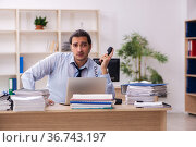 Young male employee and too much work in the office. Стоковое фото, фотограф Elnur / Фотобанк Лори