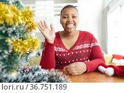 Happy african american plus size woman i making christmas video call on laptop. Стоковое фото, агентство Wavebreak Media / Фотобанк Лори