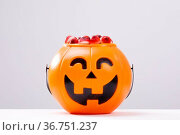 Composition of halloween bucket with trick or treat sweets on white background. Стоковое фото, агентство Wavebreak Media / Фотобанк Лори