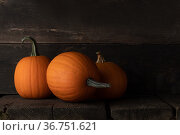 Three pumpkins on wooden background. Стоковое фото, фотограф Иван Михайлов / Фотобанк Лори