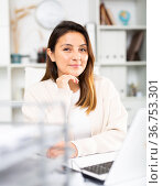 Female business consultant sits in the office in front of a laptop. Стоковое фото, фотограф Яков Филимонов / Фотобанк Лори
