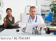 Doctor writing prescription to female patient on laptop at clinic. Стоковое фото, фотограф Яков Филимонов / Фотобанк Лори