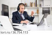 Head of the company conducts online negotiations with business partners in headphones. Стоковое фото, фотограф Яков Филимонов / Фотобанк Лори
