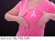 Midsection of caucasian woman in pink tshirt with pink ribbon gesturing. Стоковое фото, агентство Wavebreak Media / Фотобанк Лори