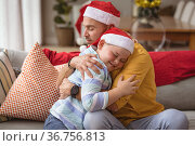 Caucasian father and son hugging each other sitting on the couch at home during christmas. Стоковое фото, агентство Wavebreak Media / Фотобанк Лори