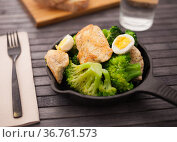 healthy appetizer of chicken pieces with broccoli and quail eggs in small cast iron skillet. Стоковое фото, фотограф Татьяна Яцевич / Фотобанк Лори