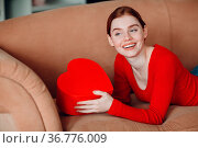 Beautifil young woman with red hair lying in her sofa in living room... Стоковое фото, фотограф Zoonar.com/Max / easy Fotostock / Фотобанк Лори