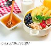 Plate with oatmeal and fruit, honey in a bowl on a white table. Healthy... Стоковое фото, фотограф Zoonar.com/DANK0 NN / easy Fotostock / Фотобанк Лори