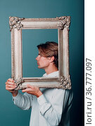 Millenial young man with blonde hair on gilded picture frame profile... Стоковое фото, фотограф Zoonar.com/Max / easy Fotostock / Фотобанк Лори