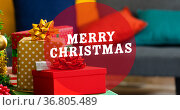 Composition of merry christmas text over presents on table. Стоковое фото, агентство Wavebreak Media / Фотобанк Лори