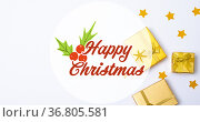Composition of happy christmas text over presents and stars on white background. Стоковое фото, агентство Wavebreak Media / Фотобанк Лори