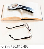 Reading book with low vision - spectacles and loupe on open book on... Стоковое фото, фотограф Zoonar.com/Valery Voennyy / easy Fotostock / Фотобанк Лори