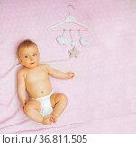 Cute baby girl and mobile toys on pink blanket. Стоковое фото, фотограф Сергей Новиков / Фотобанк Лори