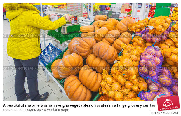 Купить «A beautiful mature woman weighs vegetables on scales in a large grocery center. Text in Russian: Auchan, scales for vegetables, onion, bulb, pumpkin, nutmeg pear, discount», фото № 30314261, снято 1 марта 2019 г. (c) Акиньшин Владимир / Фотобанк Лори