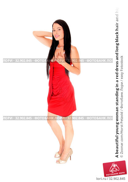 A beautiful young woman standing in a red dress and long black hair and high heels, smiling, isolated for white background. Стоковое фото, фотограф Zoonar.com/Horst Petzold / easy Fotostock / Фотобанк Лори