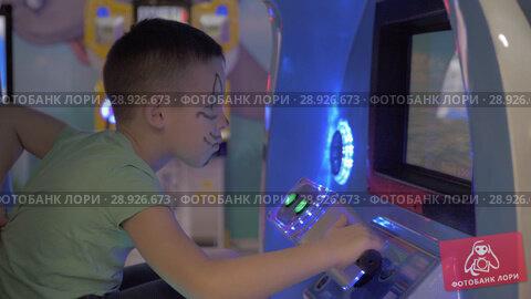 Купить «A boy in a moving game machine cabin», видеоролик № 28926673, снято 27 февраля 2018 г. (c) Данил Руденко / Фотобанк Лори