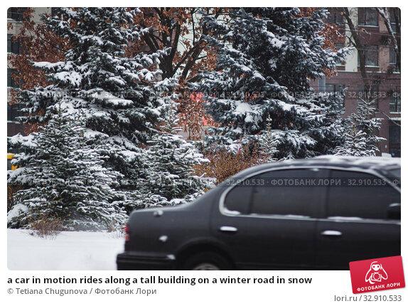 Купить «a car in motion rides along a tall building on a winter road in snow», фото № 32910533, снято 1 декабря 2018 г. (c) Tetiana Chugunova / Фотобанк Лори