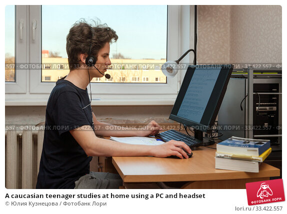 A caucasian teenager studies at home using a PC and headset. Стоковое фото, фотограф Юлия Кузнецова / Фотобанк Лори