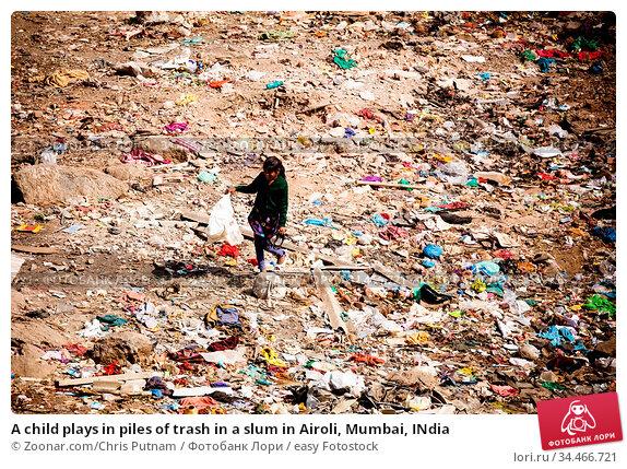 A child plays in piles of trash in a slum in Airoli, Mumbai, INdia. Стоковое фото, фотограф Zoonar.com/Chris Putnam / easy Fotostock / Фотобанк Лори