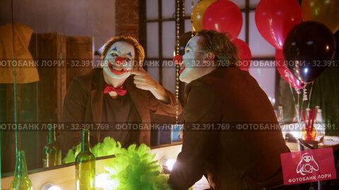 Купить «A crazy man clown in the dressing room applying his paint - drawing a smile with a red paint and smile», видеоролик № 32391769, снято 20 ноября 2019 г. (c) Константин Шишкин / Фотобанк Лори