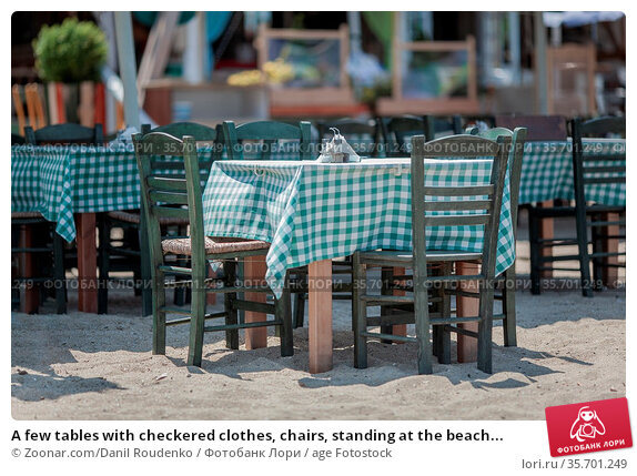 A few tables with checkered clothes, chairs, standing at the beach... Стоковое фото, фотограф Zoonar.com/Danil Roudenko / age Fotostock / Фотобанк Лори