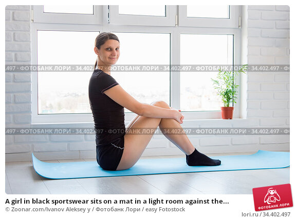 A girl in black sportswear sits on a mat in a light room against the... Стоковое фото, фотограф Zoonar.com/Ivanov Aleksey y / easy Fotostock / Фотобанк Лори