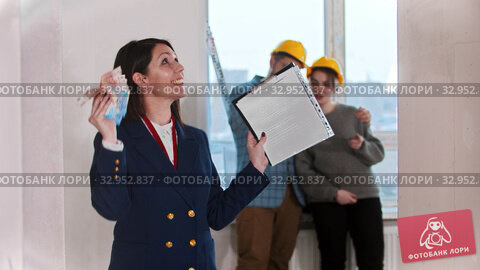 A happy real estate agent waving with cash money - young married couple looking around on the background. Стоковое видео, видеограф Константин Шишкин / Фотобанк Лори