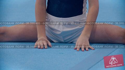 A little boy doing gymnastic exercises - sits in a split. Стоковое видео, видеограф Константин Шишкин / Фотобанк Лори