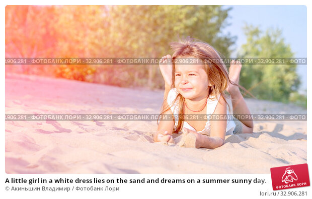A little girl in a white dress lies on the sand and dreams on a summer sunny day. Стоковое фото, фотограф Акиньшин Владимир / Фотобанк Лори