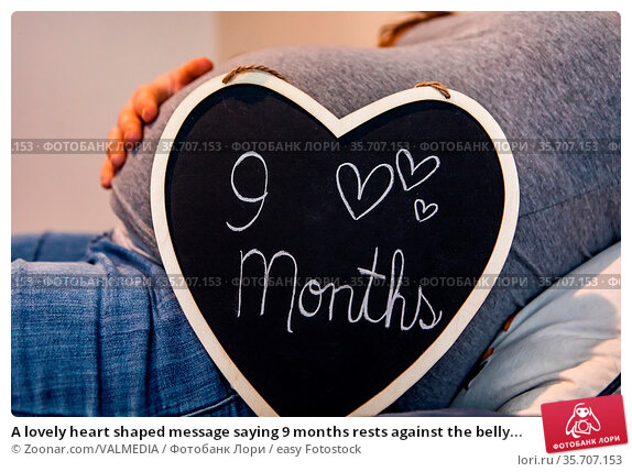 A lovely heart shaped message saying 9 months rests against the belly... Стоковое фото, фотограф Zoonar.com/VALMEDIA / easy Fotostock / Фотобанк Лори