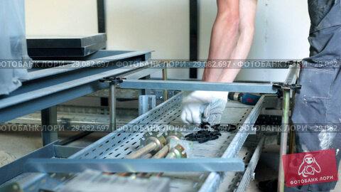 Купить «a man attaches parts to an object that looks like a cart. production. raised floor.», видеоролик № 29082697, снято 18 сентября 2018 г. (c) Константин Шишкин / Фотобанк Лори