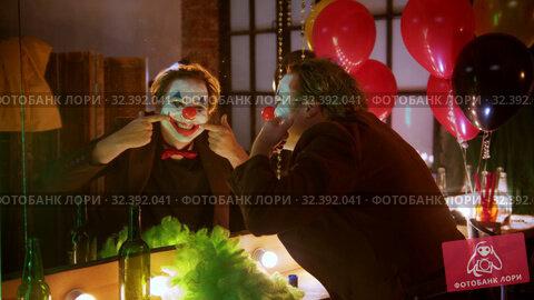 Купить «A man clown stretches out his lips in a smile and laughing at himself in the mirror», видеоролик № 32392041, снято 20 ноября 2019 г. (c) Константин Шишкин / Фотобанк Лори