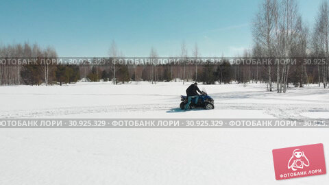 Купить «A man gets off the quad in the middle of a snow-covered field.», видеоролик № 30925329, снято 24 июня 2019 г. (c) Константин Шишкин / Фотобанк Лори