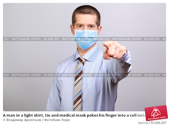 Купить «A man in a light shirt, tie and medical mask pokes his finger into a cell isolated», фото № 33439257, снято 26 марта 2020 г. (c) Владимир Арсентьев / Фотобанк Лори