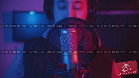 Купить «A man in hoodie rapping through the pop-filter in the microphone - recording his track in the studio», видеоролик № 32985645, снято 5 апреля 2020 г. (c) Константин Шишкин / Фотобанк Лори
