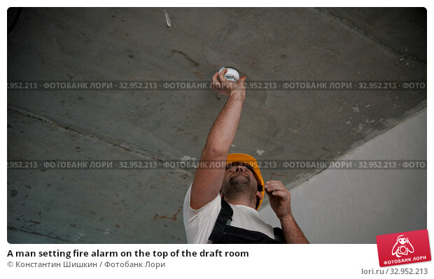 A man setting fire alarm on the top of the draft room. Стоковое фото, фотограф Константин Шишкин / Фотобанк Лори