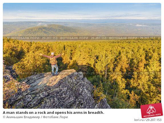 Купить «A man stands on a rock and opens his arms in breadth.», фото № 29207153, снято 6 сентября 2017 г. (c) Акиньшин Владимир / Фотобанк Лори